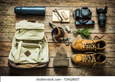 Traveling - packing (preparing) for adventure trip concept. Backpack, boots, hat, belt, thermos and camera on wooden background captured from above (flat lay).