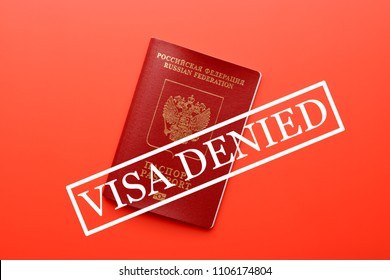 Traveling passport on top of red surface with stamp saying Visa denied on top