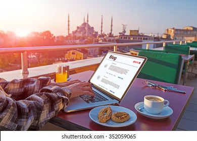 Traveling Person working on Laptop Computer at Roof Top Cafe sitting at table with Coffee Cookies and orange Juice Istanbul city Landscape on background Morning Sunlight