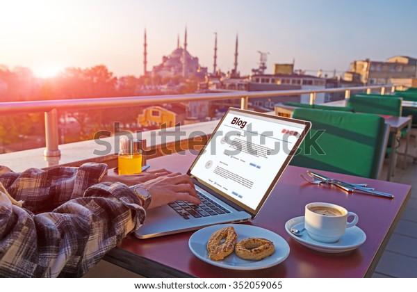 Viajero trabajando en laptop en el Café superior en mesa con cafés y zumo naranja paisajismo de Estambul en segundo plano Mañana a la luz del sol