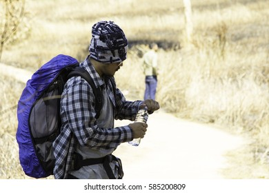 Traveling. Portrait of a young Hipster tourist wearing casual clothing and backpack standing, drinking water from bottle, Backpacker,Traveler and Tourism concept.