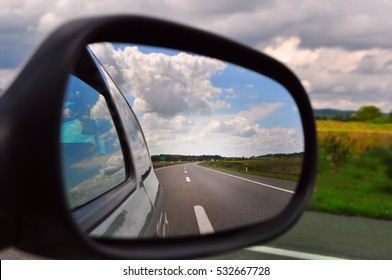 Traveling, rear view mirror road view and clouds