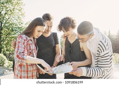 Traveling, sightseeing, group travel, city tour, student exchange program. Four friends searching the location on city map.