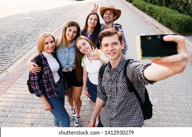 Traveling, sightseeing, group travel, city tour, student exchange program, vacation, holiday, togetherness and friendship. Happy young people taking selfie at camera in city