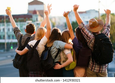 Traveling, sightseeing, group travel, city tour, student exchange program, vacation, holiday, togetherness and friendship. People with backpacks rising hands, joy and positivity