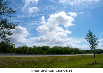 Traveling south on Interstate 95 near Mims, Florida, on a sunny day, accompanied by beautiful white cumulus clouds