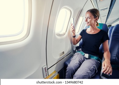 Traveling and technology. Pretty young businees woman taking photo on smartphone while sitting in airplane.