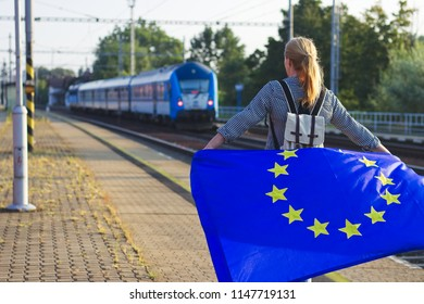 Traveling through the European Union by train. Backpacker with EU flag standing on railroad station. Travel concept.