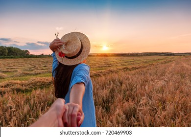 Traveling together. Follow me. Young woman in straw hat holding boyfriend's hand walking in the field on sunset