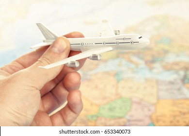 Traveling, tourism, communications and all things related - toy plane in hand with world map on background as a symbol of air transportation. Filtered image: cross processed vintage effect.
