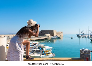 Traveling tourist woman on vacation in Heraklion Crete walking at the port. Lovely elegant girl in beige dress visiting the famous Mediterranean Venetian port. Venetian fort at background.
