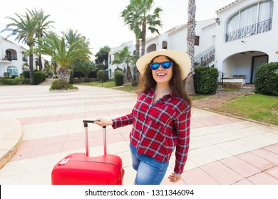 Traveling vacation, holidays, trip and people concept - woman tourist standing with suitcase when arrived in hotel