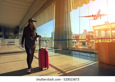 traveling woman and luggage walking in airport terminal and air plane flying outside