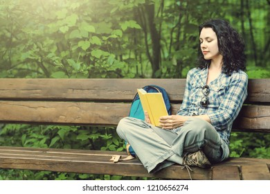 Traveling woman reading a book and relaxing at the park