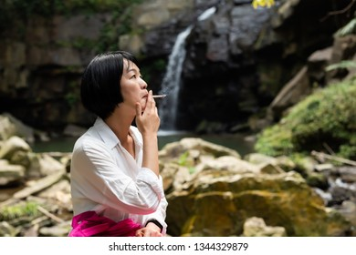 traveling woman smoking and resting near the waterfall