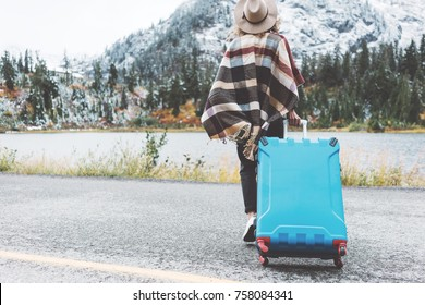 Traveling woman wearing poncho with bright blue suitcase walking to stunning mountain wild. Wanderlust and boho style