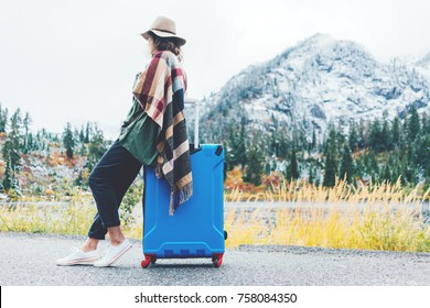 Traveling woman wearing poncho and hat sitting on her bright blue suitcase near stunning mountain wilderness. Wanderlust and boho style