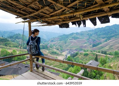 traveling young woman with backpack on the background of rice terrace in China