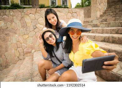 Traveller asian girls enjoy taking selfie photo with smartphone