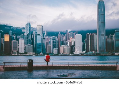 Traveller Asian male tourists sitting at the view of Victoria harbor in Hongkong in morning time, vintage tone