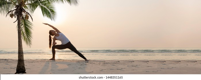 Traveller Asian woman workout and doing yoga on the beach by the palm tree at sunrise in the morning.