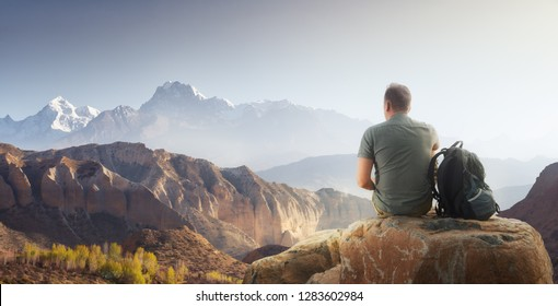 Traveller with backpack sitting on top of rock enjoying view mountains range.