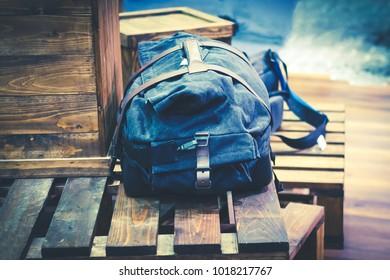 Traveller bag or backpack on wooden box image with vintage color tone