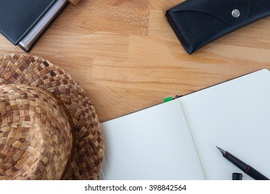 Traveller desktop, with notebook and hat on wooden table