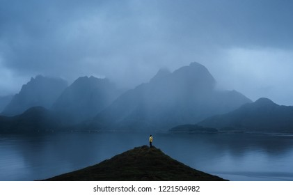 Traveller enjoying the Lofoten mountains landscape on a rainy day