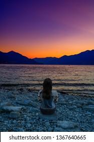 A traveller enjoying violet sunset in the port of Ascona, Switzerland