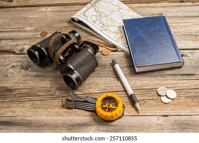 traveller equipment, items include binocullars, compass, pen, passport, map, notebook money