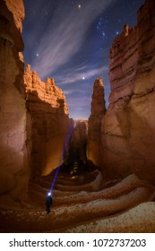 Traveller exploring Wallstreet in Bryce Canyon National Park at night. Orion Cluster under moon light.