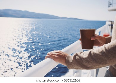 Traveller girl standing on ferry boat, looking at the sea and holding a coffee cup, travel and active lifestyle concept
