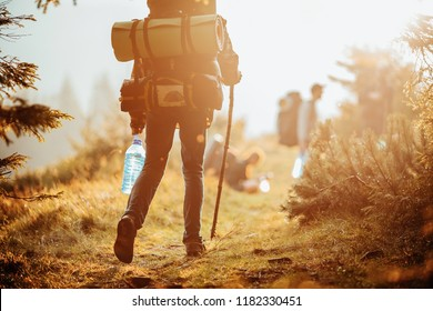 Traveller with a group hiking in the mountains at sunset.
