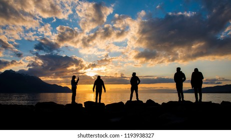 A traveller group silhouette take a photo with colorful sunset mountains background, lake Geneva, Montreax, Switzerland