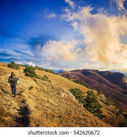 Traveller man with a backpack walks on rocky path at autumnal mountain range with dry grass and sunset sky above