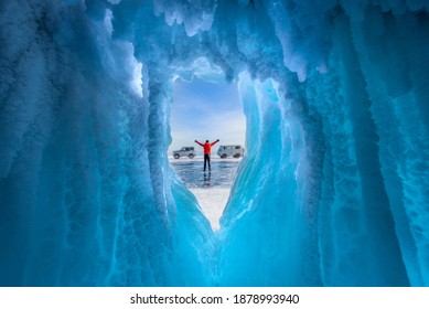 Traveller man raise up hand freedom and enjoy view of beautiful landscape natural breaking ice in frozen cave at Lake Baikal, Siberia, Russia. Travel or Freedom concept.