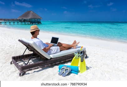 Traveller man sits on a tropical beach with his laptop and works; working in vacation concept