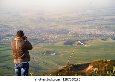 Traveller photographing mountain village and hot air balloons