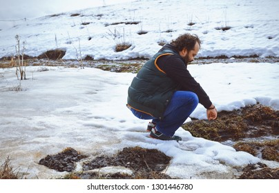 Traveller squatting at the snowy marsh
