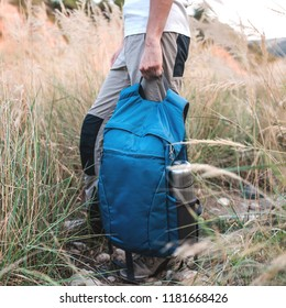 Traveller standing in the grass holds sport blue backpack and admires amazing nature around.