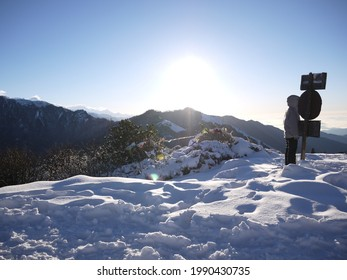 A traveller take a picture with the sign of poonhill in the sunlight and snow.