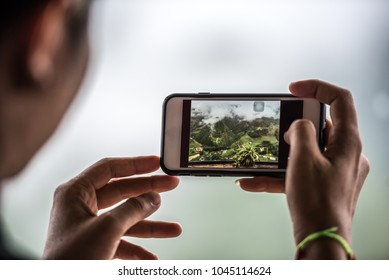 Traveller tourist hand holding mobile phone while taking a photograph of landscape in weekend, traveling take photo by mobile phone concept.
