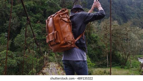 Traveller walking across an ancient abandoned dangerous bridge in the mountains