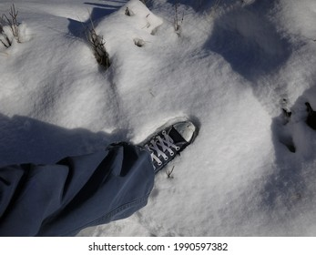 a traveller wear a canvas shoe step on the snow to show how thick it is,on the way trekking  at poonhill,nepal.
