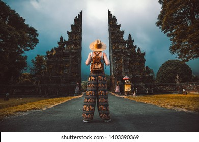 Traveller woman posing in front of a temple in Bali, Indonesia. Woman with backpack on a trip in Asia