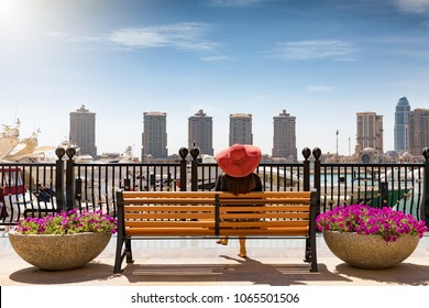 Traveller woman sits at a bench at the Pearl in Doha, Qatar and enjoys the view