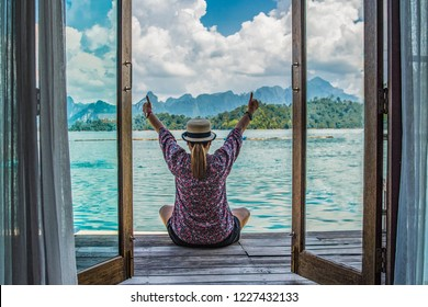 traveller woman sitting on the floor and raised arms up above head on the lake and  mountains background.