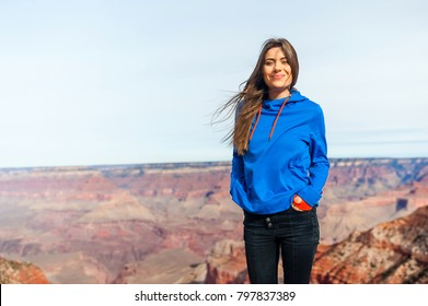 Traveller woman stands on the peak of stone at Grand Canyon viewpoint, Arizona, USA, smiling at camera in a sunny day.