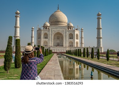 Traveller woman taking a photo by mobile phone at Taj Mahal, ivory-white marble, Agra, India.